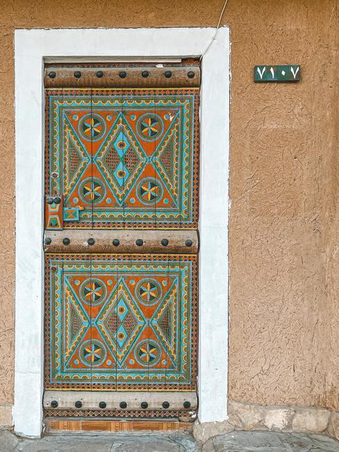 Drzwi wejściowe na których namalowane są różne wzory w kolorze turkusowym i koralowym