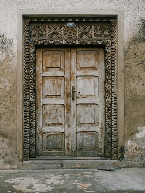 Stare drzwi wejściowe z podrapanym lakierem, wokół drzwi ozdobna wytłoczona rama
