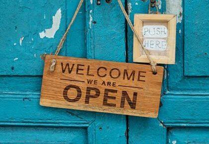 """Niebieskie drzwi z tabliczką """"zapraszamy, jesteśmy otwarci"""""""