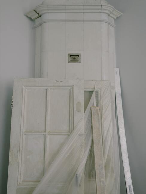 Ozdobne pomalowane na biało drzwi w pokoju pod białą ścianą