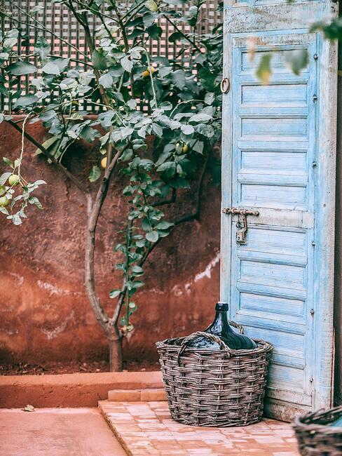 Niebieskie drzwi ze startą farbą, przed nimi wiklinowy kosz, obok drzewo