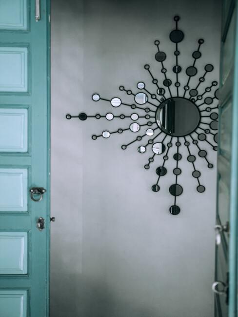 Przeszklone drzwi w turkusowym kolorze, na ścianie za drzwiami dekoracyjne lustro z czarną ramą