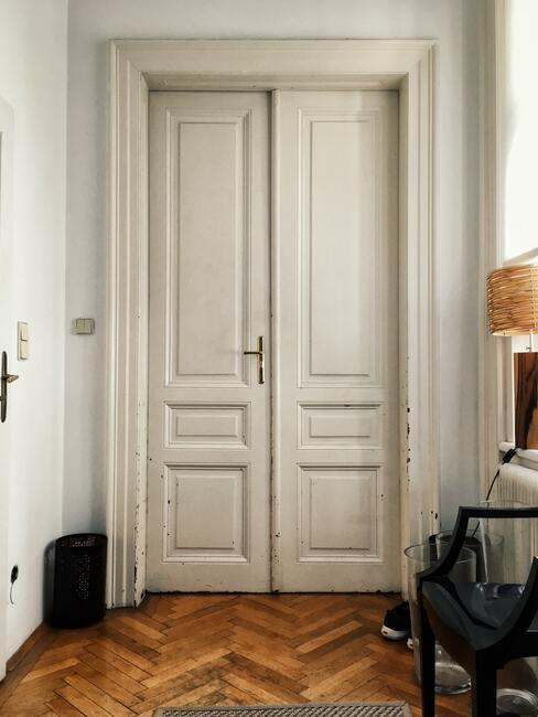 Białe drzwi w pokoju pomalowanym na biało i drewnianym parkietem