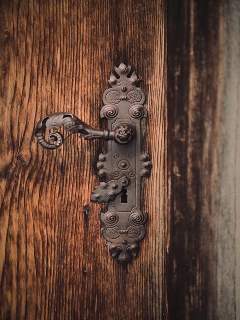 Ozdobna mosiężna zdobiona klamka na drewnianych drzwiach