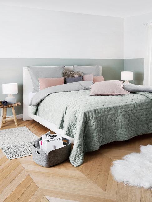 szara sypialnia z drewnianą podłogą, białym dywanikiem, i dodatkami w kolorze rózowym