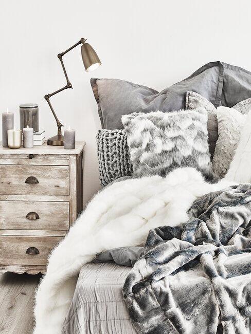 szara sypialnia: Sypialnia z szarymi tekstyliami i białą ozdobną szafka nocną z postarzanego bielonego drewna