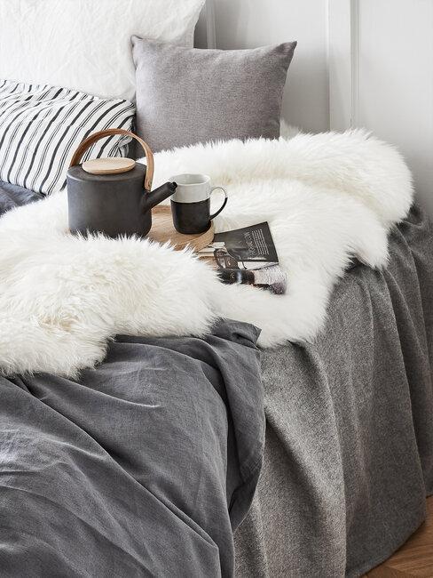 szara sypialnia: tekstylia w kolorze szarym, na łózku biały pluszowy koc i taca z dzbankiem i kubkami