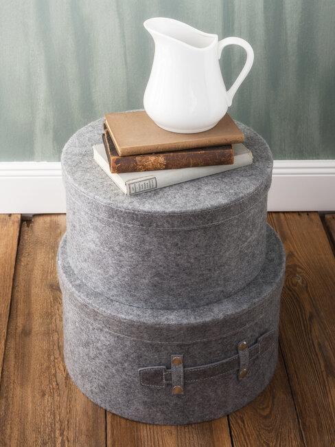 Dwa pudełka w szarym kolorze na których leżą książki i biały dzbanek
