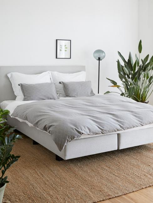 Minimalistyczna sypialnia z pościelą w kolorze szarym, białym łóżkiem i drewnianą pdłogą