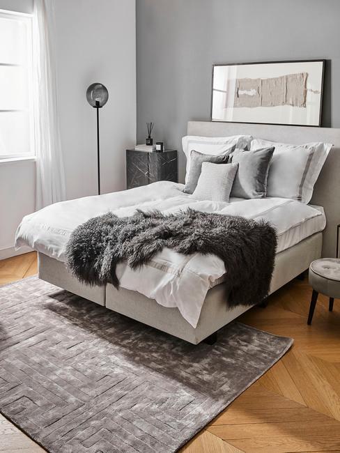 Sypialnia z białym łóżkiem, drewnianą podłoga i jedną szara ścianą, na łóżku białą pościel, poduszki dekoracyjne w szarym kolorze