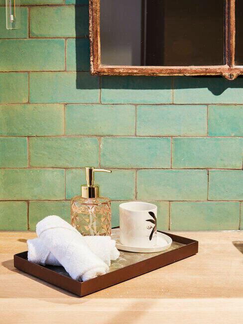 Zielona łazienka z drewniana tacką i innymi dodatkami