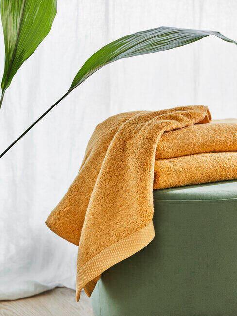 Ręczniki w kolorze pomarańczowym leżące na zielonym pufie obok rośliny