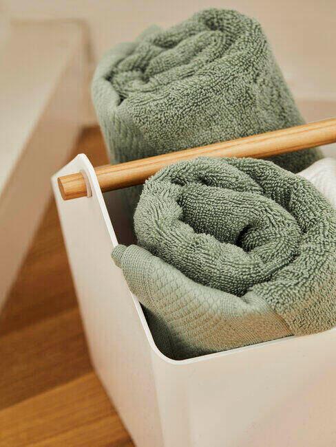 Ręczniki w odcieniu zieleni w drewnianym pojemniku