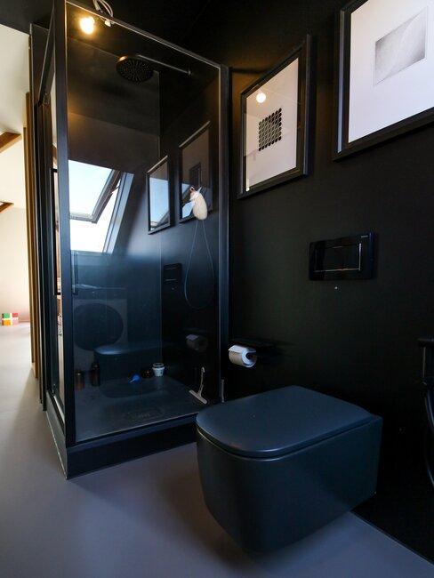Łazienka z czarnym prysznicem i obrazami na ścianach