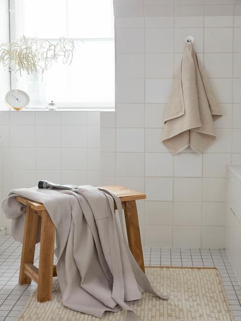 drewniany stołek z ręcznikiem w białej łazience