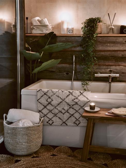 łazienka biała z drewnem: Łazienka z płytkami na ścianie w kształcie drewnianych ciemnych desek , białą wanną i dodatkami w stylu boho