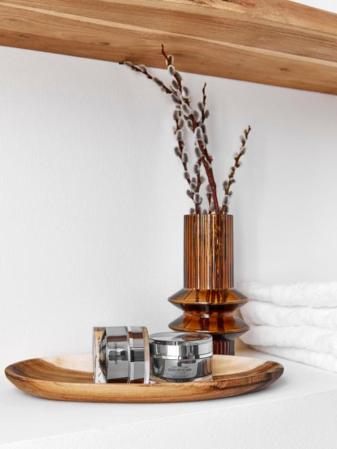 łazienka biała z drewnem: drewniana taca w łazience na której stoją kosmetyki i wazon z ciemnego szkła