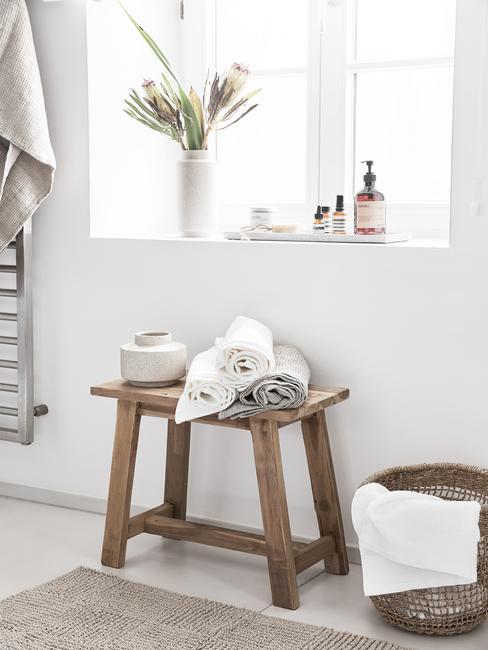 łazienka biała z drewnem: Drewniany stołek w łazience na którym leżą ręczniki