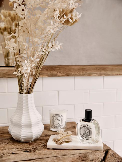 Drewniany blat w łazience na którym stoją kosmetyki i biały wazon z ususzoną trawą, w tle lustro w drewnianej ramie