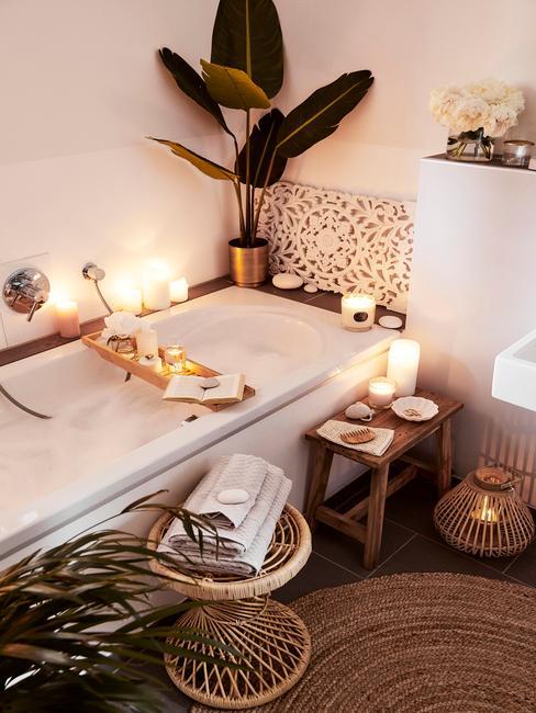 łazienka biała z drewnem: Zabudowana biała wanna w łazience, wokół świeczki i dodatki w stylu boho