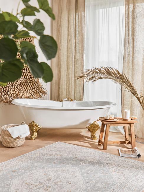 łazienka biała z drewnem: Biała wolnostojąca wanna, w łazience z bezowymi płytkami na podłodze, dodatkami w stylu boho i bezowymi zasłonami w oknie