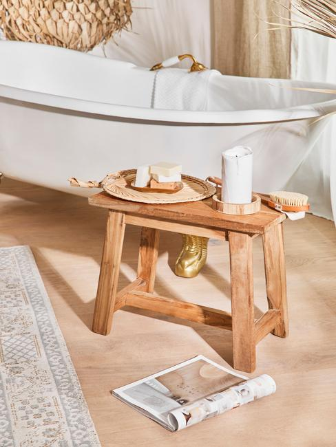 Drewniany stołek na bezowej podłodze w łazience, w tle biała wolnostojąca wanna