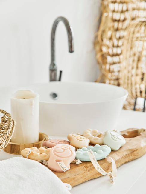 łazienka biała z drewnem: Drewniana taca w łazience na której leżą akcesoria do kąpieli i świeca