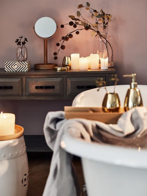 Drewniana konsola z szufladami w łazience na której stoi lustro i kosmetyki, na pierwszym planie biała wolnostojąca wanna ze złotymi akcesoriami łazienkowymi