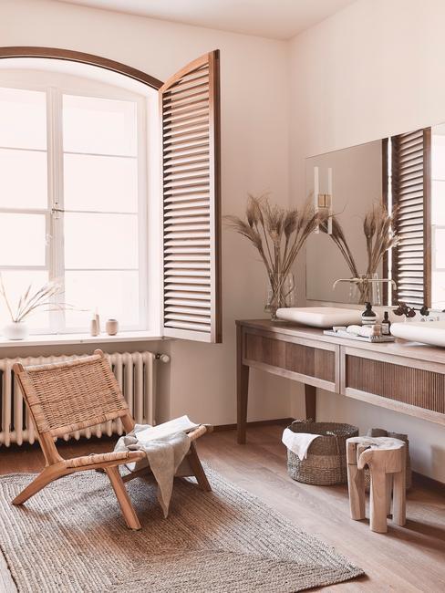 łazienka biała z drewnem: drewniana konsola w łazience z dużym oknem, obok okna drewniane krzesło z ręcznikiem