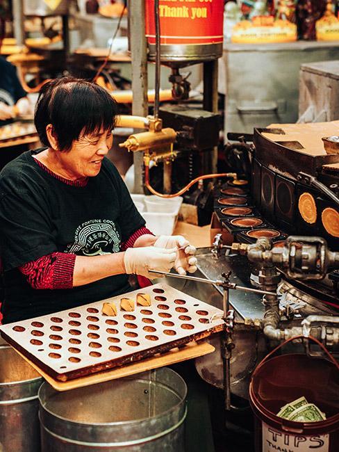 wróżby andrzejkowe: Starsza kobieta pochodzenia azjatyckiego produkująca ciasteczka z wróżbą