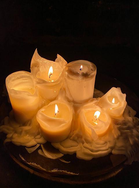 wróżby andrzejkowe: zapalone białe świeczki w ciemnym pokoju