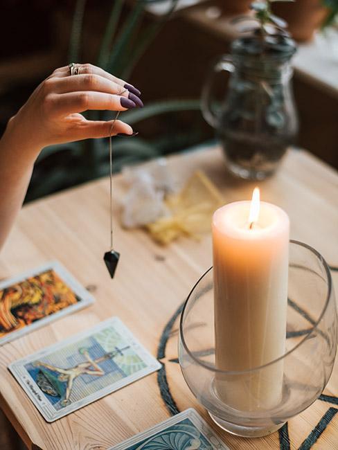 wróżby andrzejkowe: Biała świeca na stole przy którym siedzi osoba trzymająca w dłoni amulet