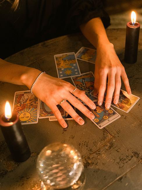 wróżby andrzejkowe: Dłonie położone na stole nad kartami tarot