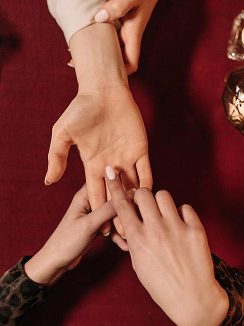 Dwie osoby trzymające się za ręce, jedna wróży drugiej z ręki