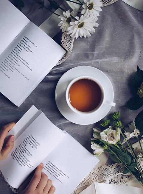 Filiżanka kawy lub herbaty na szarej narrucie obok książek