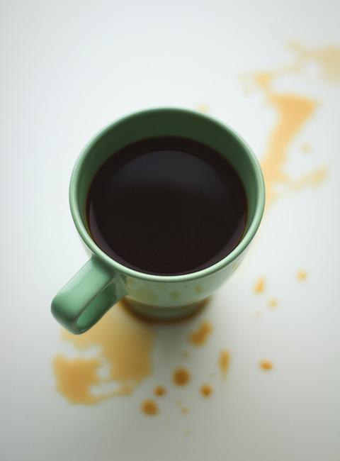 Plamy z kawy na blacie stołu obok kubka