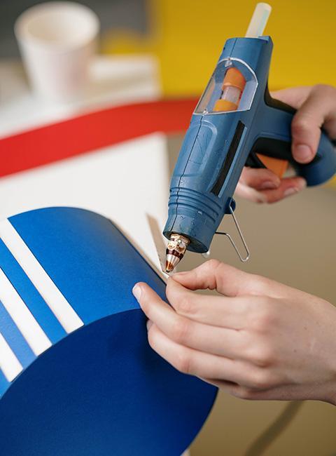 Zbliżenie na dłonie dekorujące niebieski klosz za pomocą pistoletu do kleju