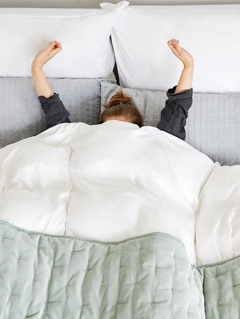 Kobieta budząca się w łóżku z zieloną narzutą