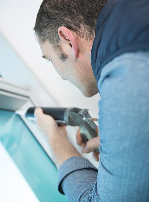 Mężczyzna izolujący okno silikonem