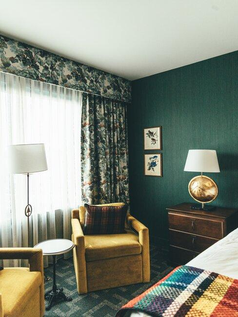 Wnętrze zielonej sypialni, w centrum fotel i lampa