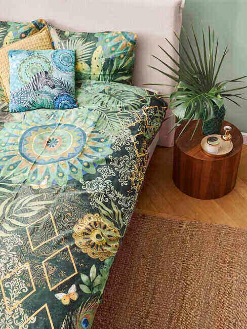 Łóżko przykryte narzutą w zielone wzory