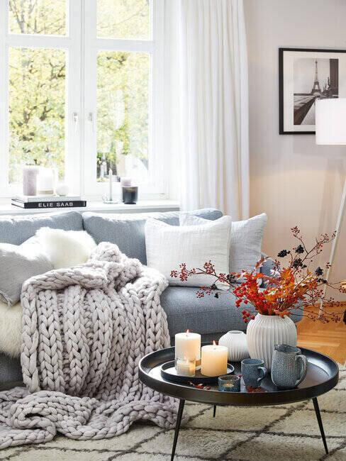 Ujęcie na stolik w salonie, obok kanapa z kocem