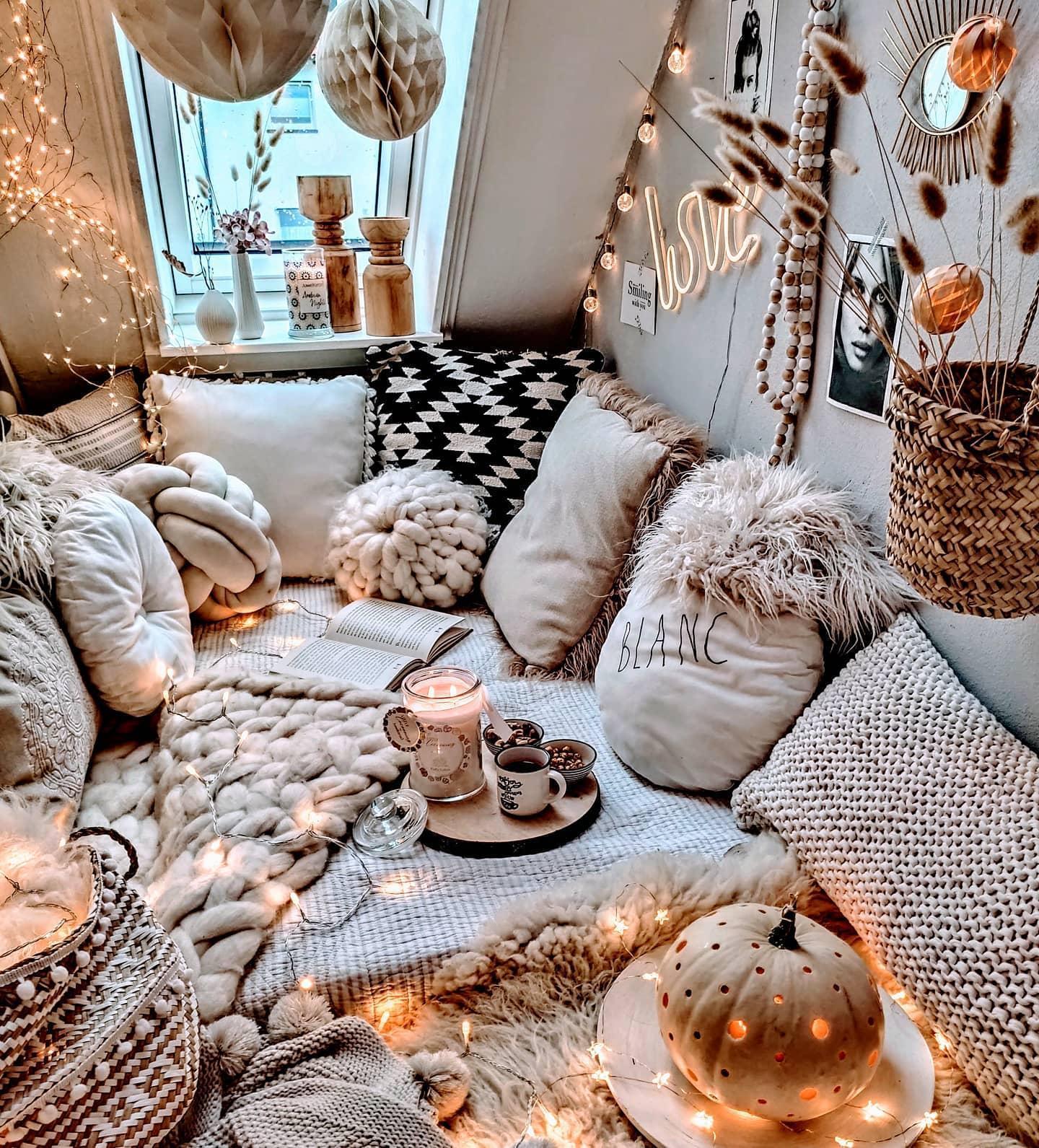 Prztulne jesienne wnętrze w stylu boho z licznymi poduszkami i lampkami
