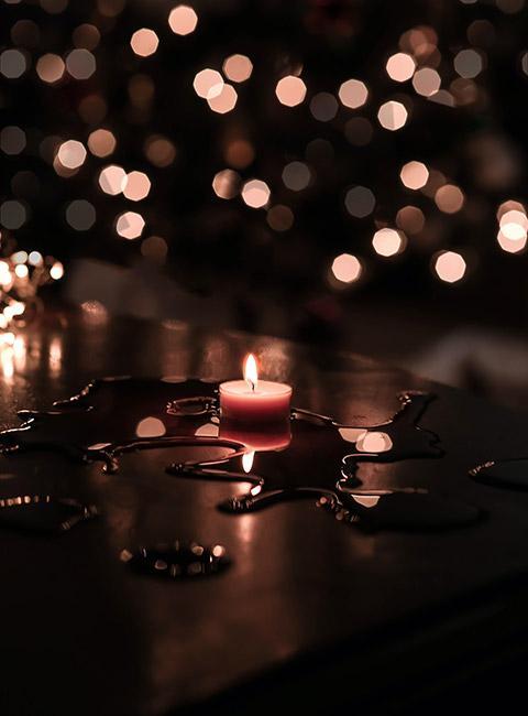 świeczka tealight na stole z rozlanym woskiem zświatełkami w tle