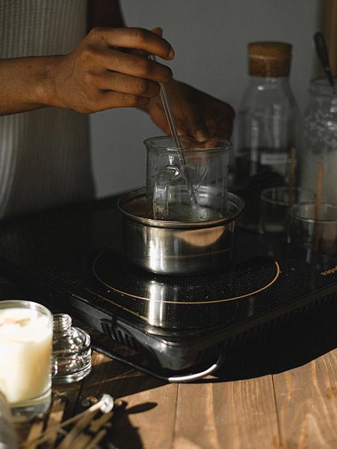 Zbliżenie na dłonie topiące wosk w garnuszku