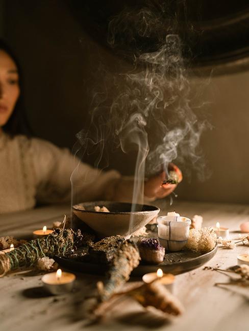 wróżby andrzejkowe: Osoba zapalająca małe kadzidełko