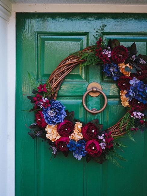 Wieniec wiosenny na zielonych drzwiach wejściowych