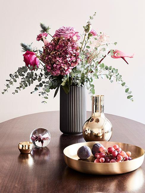 Złota miska z owocami na drewnianym stole obok szarego wazonu z bukietem kwiatów