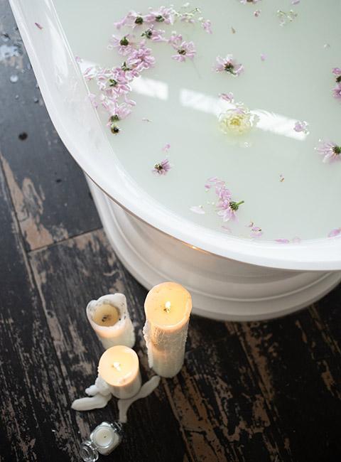 Świeczki palące się obok wanny napełnionej wodą z płatkami kwiatów