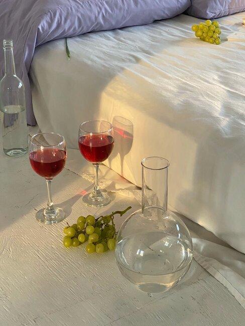 Dwa kieliszki wina stojące obok łóżka